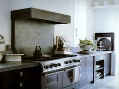 Cozinha com moveis escuros e paredes brancas