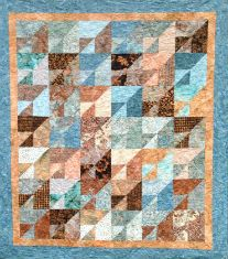 """Batik version of """"Attic Mirror"""" quilt, made from 10"""" squares.  A Warped Spinster design."""