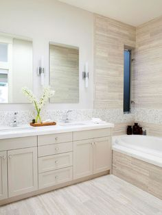 Clean lines and a monochromatic color palette create a soothing yet stylish bathroom. Ceramic tiles give the illusion of vein-cut travertine and add high visual impact to the space./