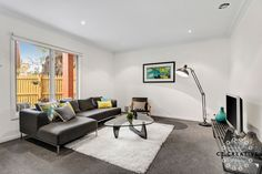 Charcoal couch, yellow and blue colour accents.  Living room ideas.  Photography by CT Creative.