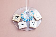 """Today, April is """"Scrabble Day."""" DIY these cute wine markers with old scrabble tiles. Scrabble Tile Crafts, Scrabble Letters, Wine Bottle Tiki Torch, Tribute, Tiki Torches, Wine Glass Charms, Bottle Charms, Game Pieces, Puzzle Pieces"""