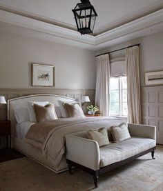Montreal designer Julie Charbonneau went with a soft palette of taupe and beige for this feminine bedroom. The panelling on the lower half of the wall is painted darkest, upper wall colour a lighter shade, and the crown moulding a warm shade of white, drawing the eye upwards from the panelling. Charbonneau also added a bold black light fixture and curtain rod to ground the lightness of the room.: