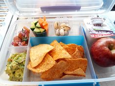 Corn chips with fresh salsa, guacamole, cucumber and carrot sticks, pistachios and almonds, yogurt and an apple.