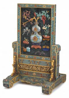 Chinese spinach jade and cloisonne 'da ji' table screen  The rectangular removable table screen depicts a double gourd vase holding peony sprigs, lychee fruits, and surrounded by pomogranate, grapes, books and other auspicious items, all secured within a cloisonne enameled frame and stand.   H of screen and stand: 19 1/4 inches