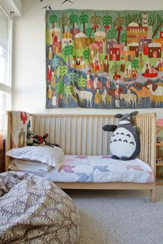 another sample of kids room with natural wood crib/bed, white walls, and multi-coloured things on walls/in room