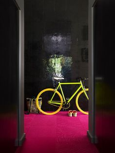 Yellow bike, black walls, pink floor
