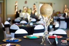 Super Hero themed wedding done with a bit of elegance.  Black linens, mixed primary color napkins, glass flute centerpiece with gold superhero's climbing to a glittered gold sphere and fairy lights!  #superherowedding #superheroparty #superherolove #specialoccasionsgp