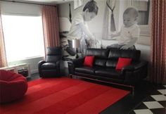 a beautiful living room with black sofas and red carpet with a beautiful background