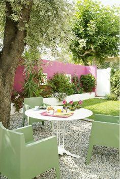 Simplicidade com o piso de brita e o destaque da parede rosa
