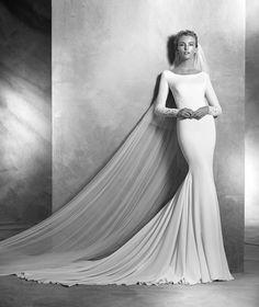 Vestido de novia de crepe de estilo sirena con aplicaciones de encaje con manga larga. Cuerpo de escote redondo con aplicaciones de encaje en manga y cuerpo.