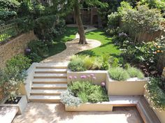 different levels, path taking you on a journey, raised beds, colours, inbuilt bench, lots of interest