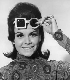 Headshot portrait of American actor and singer Annette Funicello lifting up her sunglasses and smiling, She wears a blouse with peacock plume pattern. Her sunglasses have one square and one circular lens. Annette Funicello, Michael Kors Designer, Catherine Deneuve, Sharon Tate, Twiggy, Lancaster, Ray Bans, Fashion Bubbles, White Sunglasses