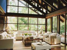 Salón con paredes y techo de estilo cabaña con cristalera hacia el jardín