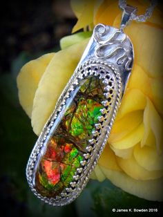 An opal like fossil ammonite shell fragment that was cabbed and set in sterling silver by James K. Bowden.  #ammolite #ammonite #gem #gemstone #lapidary #silversmithing #silver #jewelry