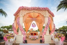 An outdoor mandap in pastel pinkish-peach color featuring matching drapes along the pillars and ceiling and garlands of pink and orange blossoms by Fascinate by Jessy for Karishma and Manish #weddingsutra #indianweddings #mandap #decorideas #florals #weddingflorals #drapes #weddingdecor #floralmandap #indianbride #indiangroom #weddingplanning #intimateweddings #outdoorweddings #colourful #streamers #decor #flowers #lights Photos courtesy: The Wedding Story