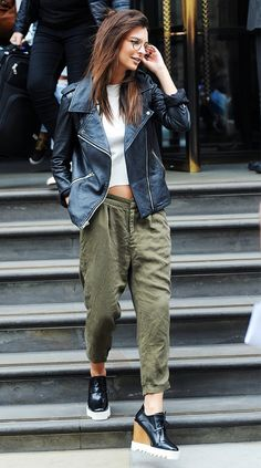 Emily Ratajkowski wears a crop top, cargo pants, a leather motorcycle jacket, and Stella McCartney wedges