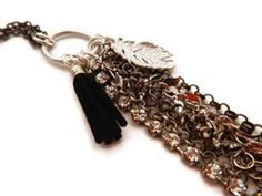 Leather & Feather necklace.  Mixed silver metals, crystals and leather in a long, flowing necklace.  www.jewelrybyandrea.com