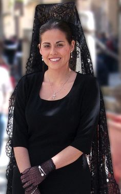 Spanish woman wearing traditional mantilla and peineta, veil and comb.