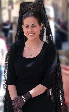 Spanish woman wearing traditional mantilla and peineta, veil and comb.