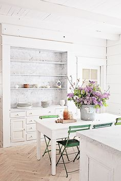 The perfect dreamy white French farmhouse style kitchen with built-ins, carrara marble subway tiles, oak herringbone floors, white farm table, green bistro chairs, and vintage accessories! 50 Details to Love in Maria's Dreamy Whites French Farmhouse Kitchen {Decor Inspiration} - Hello Lovely