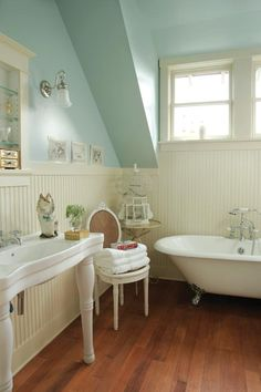 charming bath .    A reproduction tub and sink are flanked by beadboard in the master bath.