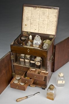 The mahogany medicine chest contains boxes, bottles and tubes of medications to treat a number of conditions. The chest includes treatments to purge the body by vomiting, by sweating, as well as general purgatives. Other medications include pain relief, plus astringents and stimulants. The chest contains an inventory listing the medications. The chest also includes a set of scales, weights, a pill tile and a spatula. The set was probably used in the home or by a chemist or apothecary.