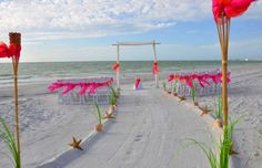 Tangerine & fuschia two post arch ... a perfect contrast to the beach which pops with vibrant color