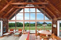 Living room with vintage Risom furniture and sliding steel door on Block Island, via Dwell Magazine.