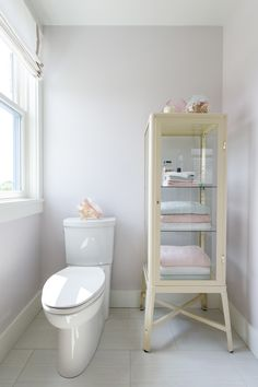 A retro glass cabinet by IKEA handily houses extra towels and bath accessories. Clean ActiVate toilet by American Standard and Roman shades by Smith & Noble.
