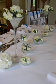 Tall martini vases of white roses, white calla lily, white freesia and blue eryngium - Cain Manor Vasetti per centro tavola Table Mariage Vase Martini, Martini Glass Centerpiece, White Centerpiece, Shower Centerpieces, Floral Centerpieces, Wedding Centerpieces, Wedding Table, Modern Flower Arrangements, Wedding Arrangements