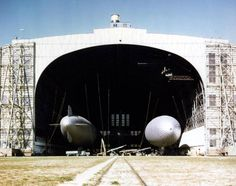 "Naval Air Station, Lakehurst, New Jersey. ""K"" Type Blimps in one of the air station's airship hangars, circa 1942-43. Blimp at right is the K-7. Photographed by Miller. National Archives photograph, 80-G-K-15413 (Color)."