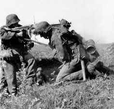 German soldier open the fire instantly with your MG 42, using the shoulder of his loader, against soviet infantry during the Battle of Kursk, July 1943.