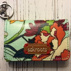Sakroots key chain ID wallet Sakroots flap ID key chain with a coated canvas featuring a snap closure, exterior clear ID window, key ring with dog clip, interior zip pocket, and single credit card slot. Dimensions: 3.25H x 4.75W x .75D. Sak Bags Wallets