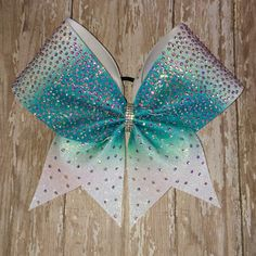 Badda Bling Bows provides the highest quality bows on the market specializing in individual, practice and team bows and we uniform match! This gorgeous ombré cheer bow is covered with over over 1,400 AB crystals! Sublimated on white glitter gives this gorgeous bow a beautiful sparkly effect with crisp vibrant color! Available in any color combo.  �� Made with 3 ribbon �� Packaged and shipped in a box to ensure it arrives in perfect condition.  �� FREE shipping and discounts on team orders…