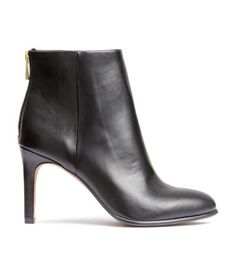 Ankle boots in imitation leather with pointed toes, zip at back, satin lining, and rubber soles. Heel height 3 3/4 in.