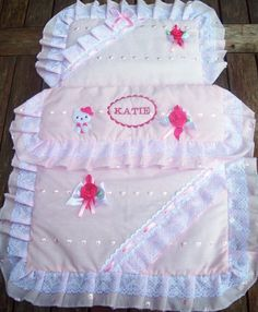 A personalised Silver Cross pram & quilt set.  This beautiful set is made from a lovely pink brodery anglaise cotton fabric, frilled with white lace, embellished with satin bows and finished with a cute Hello Kitty.