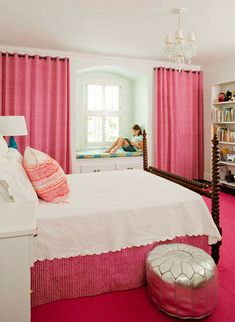 A pink bedroom with pretty pink curtains and carpets.