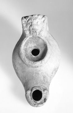 Clay lamp; orange-brown clay; mica; shoulder: plain; small volutes near wick-hole; discus - plain; broad handle decorated with lions head; base-ring: impressed footprint stamp. Culture/periodEarly Byzantine term details Date500-600 (circa) Production placeMade in: Turkey