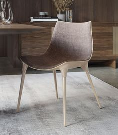 The award-winning Langham dining chair features modern curves with mid-century flare. Chair features fiberglass bucket seat construction with either Brazilian wood or painted steel legs. Padded seat finished in viscose blended fabric upholstery. COM available for contract orders.