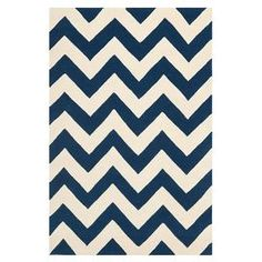 Hand-tufted wool rug with a bold chevron motif.    Product: RugConstruction Material: WoolColor: Dark blue and ivoryFeatures:  Made in IndiaHand-tufted Note: Please be aware that actual colors may vary from those shown on your screen. Accent rugs may also not show the entire pattern that the corresponding area rugs have.Cleaning and Care: Professional cleaning recommended