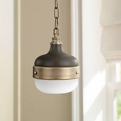 Finished in matte black with dark antique brass hardware and accents, this mini pendant look is inspired by industrial design.