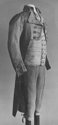 Pair of knee-breeches of machine-knitted beige silk. Pattern of vertical stripes. At the top are nine flat white metal buttons. At each knee are three small buttons covered with the same-coloured silk, and linen tapes for tying. There is a linen band as lining at waist.