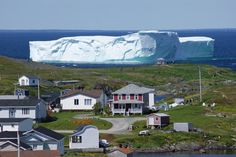 """An impressive iceberg arrived in Newfoundland's Goose Cove in mid-July. """"Icebergs float in from Greenland,"""" said the photographer, Gene Patey. This one briefly blocked the town's harbor before breaking apart and melting, """"but the fishermen took their chances."""" (Photo: Gene Patey)"""