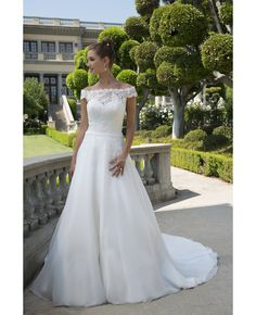 Lace Bodice Straight neckline with off the shoulder short sleeves has a belt accent at waistline beautiful high straight across illusion back A line gown with a semi cathedral train    Fabric(s): Lace/Organza    Color Available: Ivory/Nude, IV/IV    Size: 2 to 33