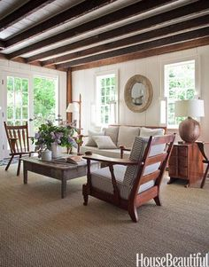 Rustic and Refined  Designer Shawn Henderson updated the living room of this 1830s colonial farmhouse in Hillsdale, New York, by painting the wood walls white but leaving the ceiling beams dark. Then he filled the space with furniture picked up at yard sales and antique stores.