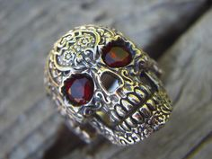 Sale....Sugar skull ring in sterling silver with blood red cz's for eyes. $135.00, via Etsy.