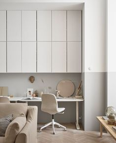 Lots of overhead wall cabinets create lots of storage space for a workspace in the living room.
