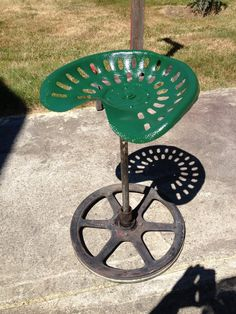 Old tractor seat, fresh paint. Old fly wheel for base and 1in pipe. Welded together.