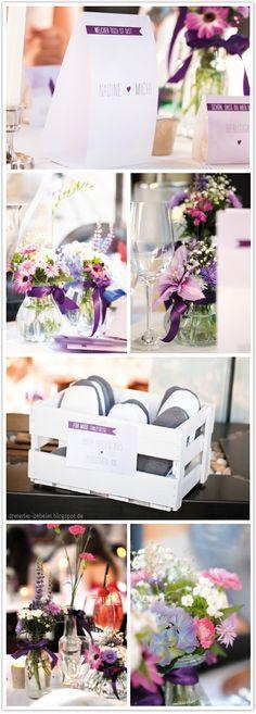 Glasvasen mit Schleifenband umwickeln und mit Farbmottopassenden Blumen füllen