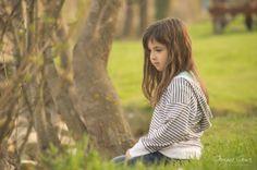 Beautiful little girl sitting on the grass